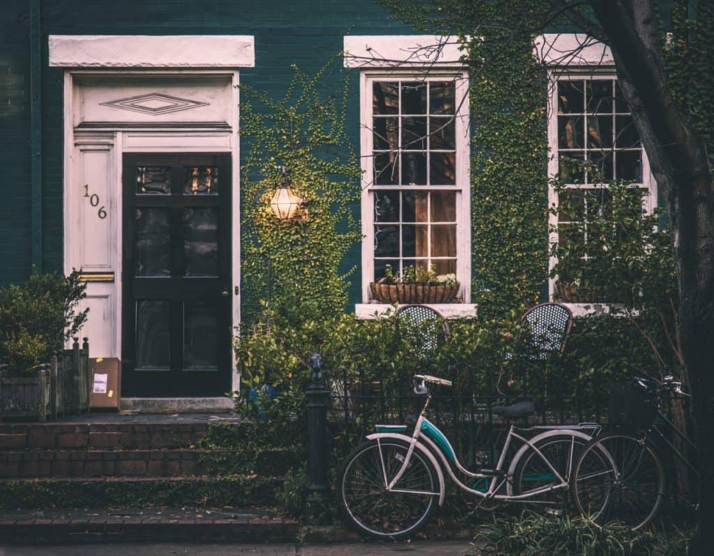 Imagem de bicicletas encostas em frente a uma casa.