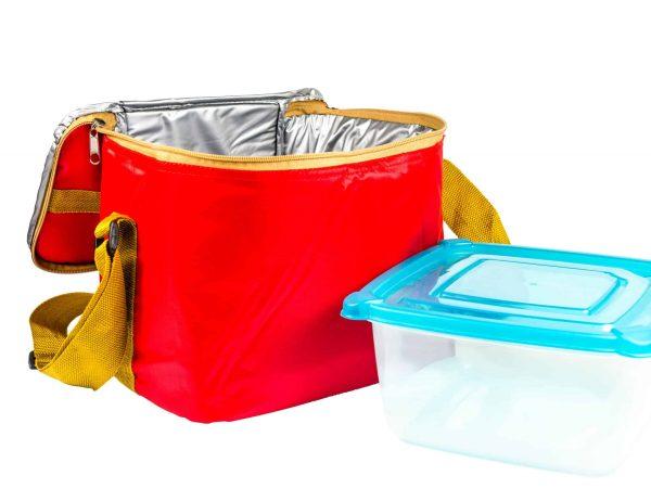 Bolsa térmica vermelha e pote de plástico com tampa azul ao lado.