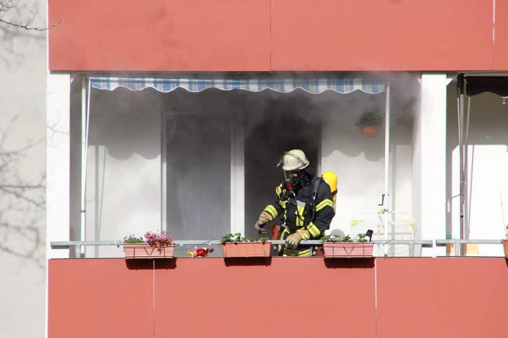 Bombeiro em sacada de apartamento. Ao fundo, na janela da sacada, grande quantidade de fumaça é liberada.