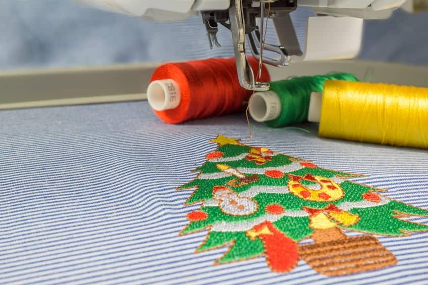 Imagem de bordado de máquina de árvore de natal e linhas ao fundo.