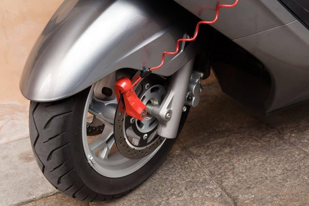 Imagem mostra mostra em close o pneu de uma moto estacionada com cadeado e cordão de lembrete.