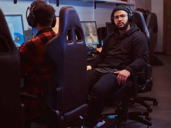 Imagem de dois homens sentados em cadeira gamer preta.