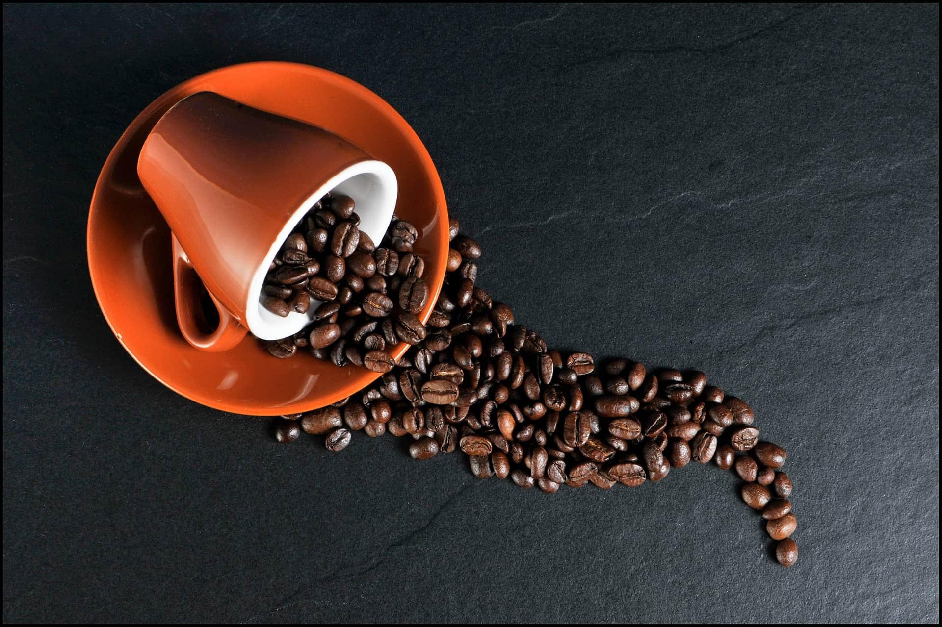 Xícara de café vermelha com grãos espalhados.