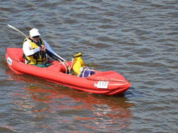 Homem rema sozinho em caiaque inflável vermelho de dois lugares.
