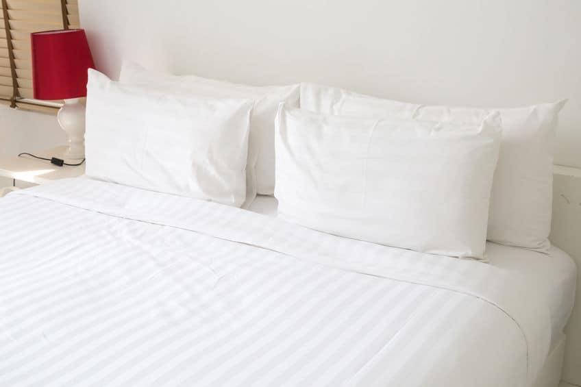 Lençol branco esticado em cama.