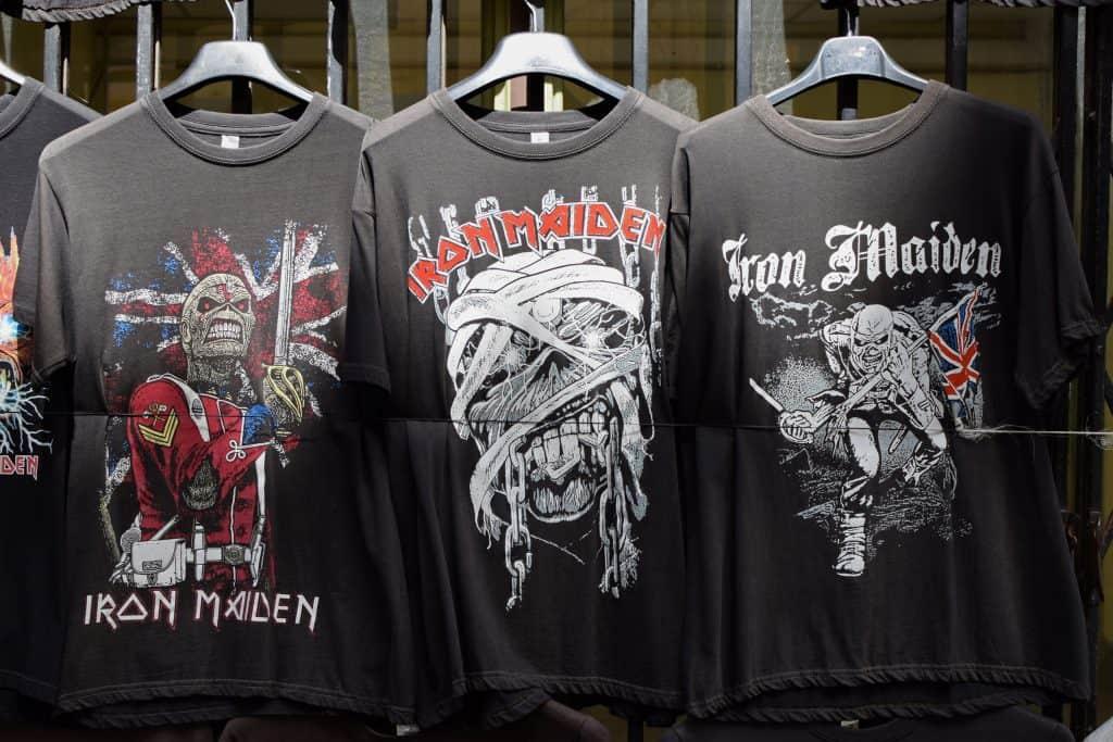 Foto de três camisetas pretas do iron maiden penduradas no cabide uma ao lado da outra.