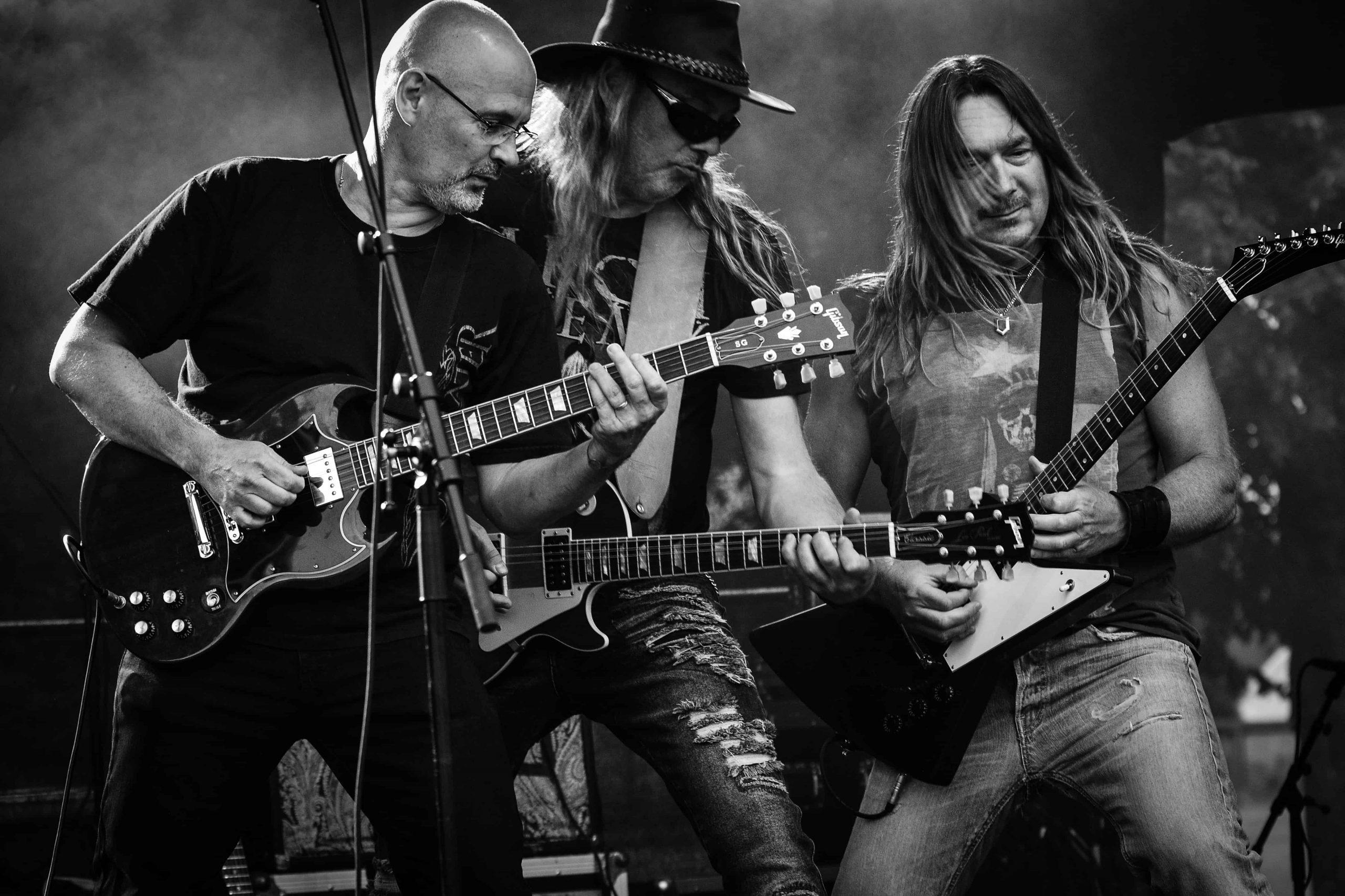 Imagem de três homens tocando em banda e utilizando camisetas estampadas.