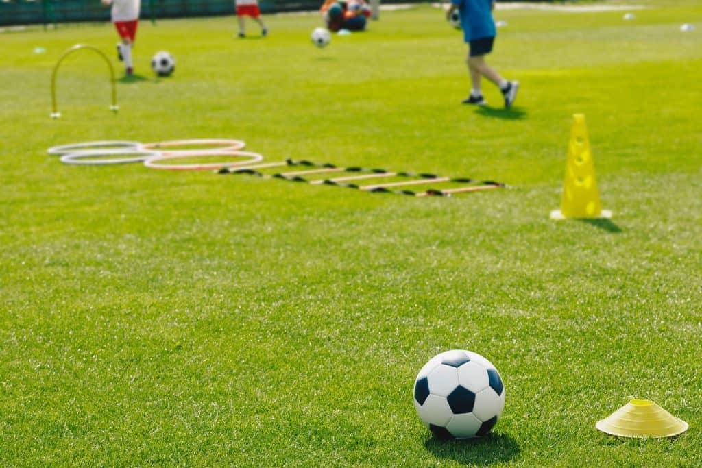 Escada de agilidade estendida no gramado perto de cone, bola de futebol e argolas.
