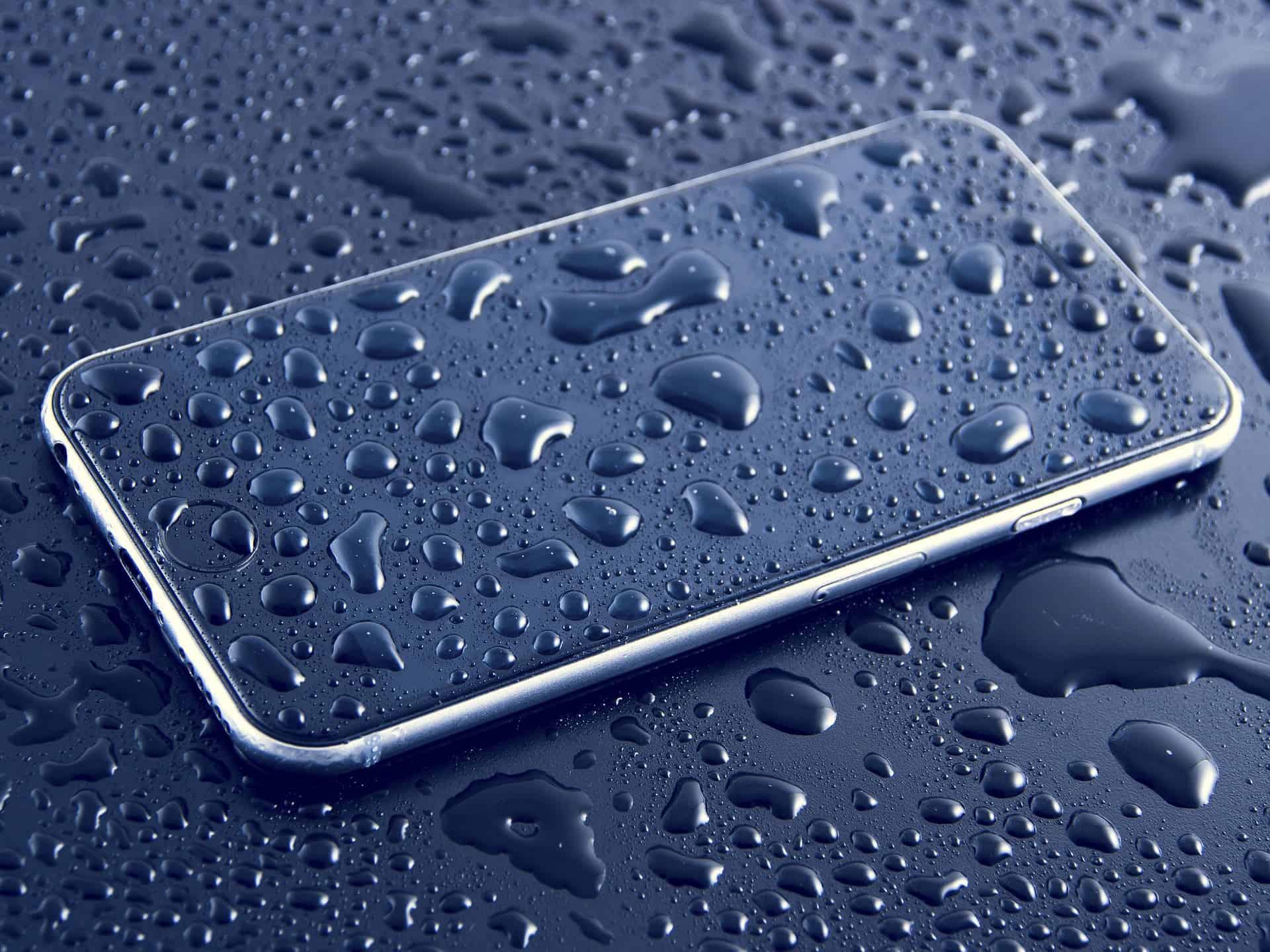 Imagem de aparelho celular coberto de respingos de água.