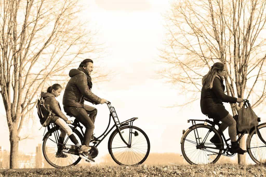Imagem de homem e mulher andando de bicicleta com criança andando na garupa de uma das bicicletas.