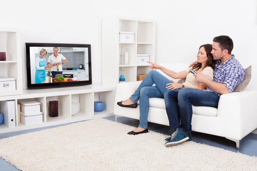 Imagem de casal assistindo TV.