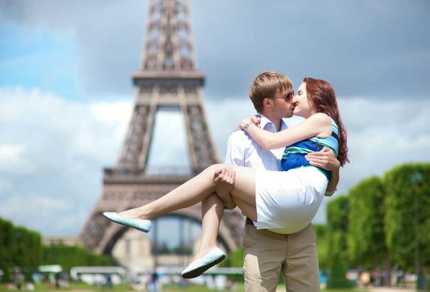 Foto de um homem segurando uma mulher no colo e beijando-a em frente a torre Eiffel em Paris.