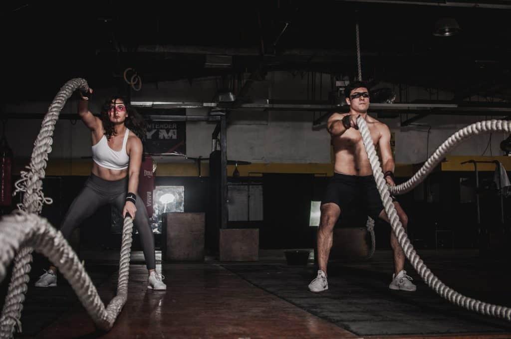Homem e mulher treinando crossfit lado a lado usando cordas navais.