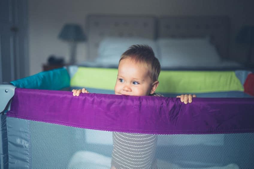 Imagem de um bebê em pé dentro de um cercadinho.