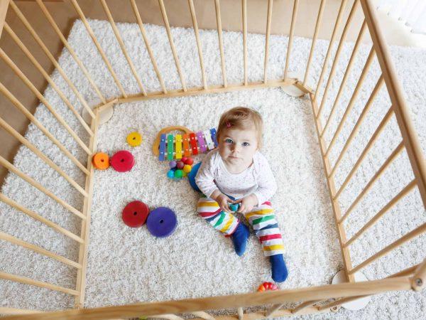 Imagem de bebê dentro de cercado com brinquedos.