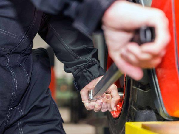 Um mecânico usando uma chave de roda em um parafuso de uma roda de um carro.