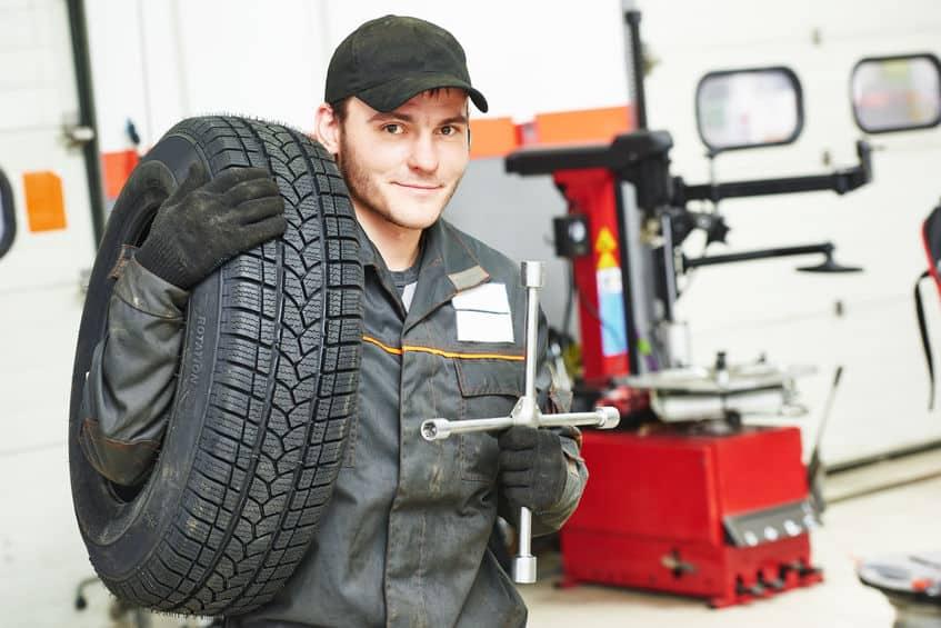 Em uma oficina mecânica um mecânico está segurando um pneu grande com uma mão e uma chave de roda com a outra mão.