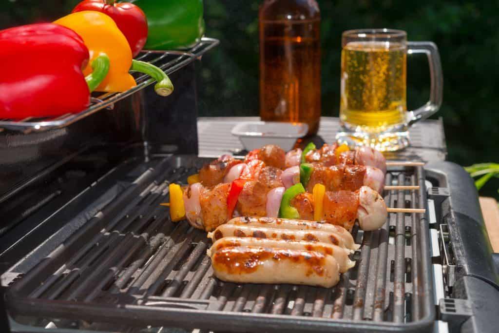 Carne e legumes sendo preparados em churrasqueira elétrica.