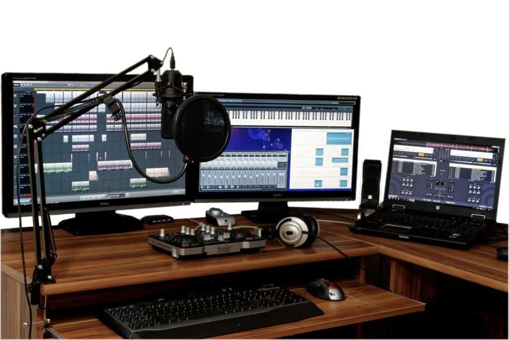 Imagem de três computadores formando uma ilha de edição musical.
