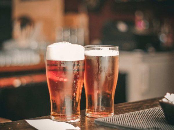 Foto de dois cheios copos de cerveja, um com e um sem colarinho, em um balcão de um local que se assemelha com um bar.