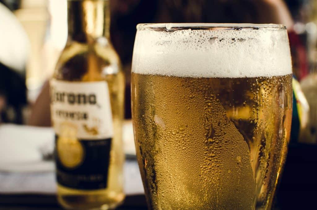 Em primeiro plano, a foto do topo de um copo de cerveja, cheio, com aspecto gelado. Em segundo plano, uma long neck de Corona.