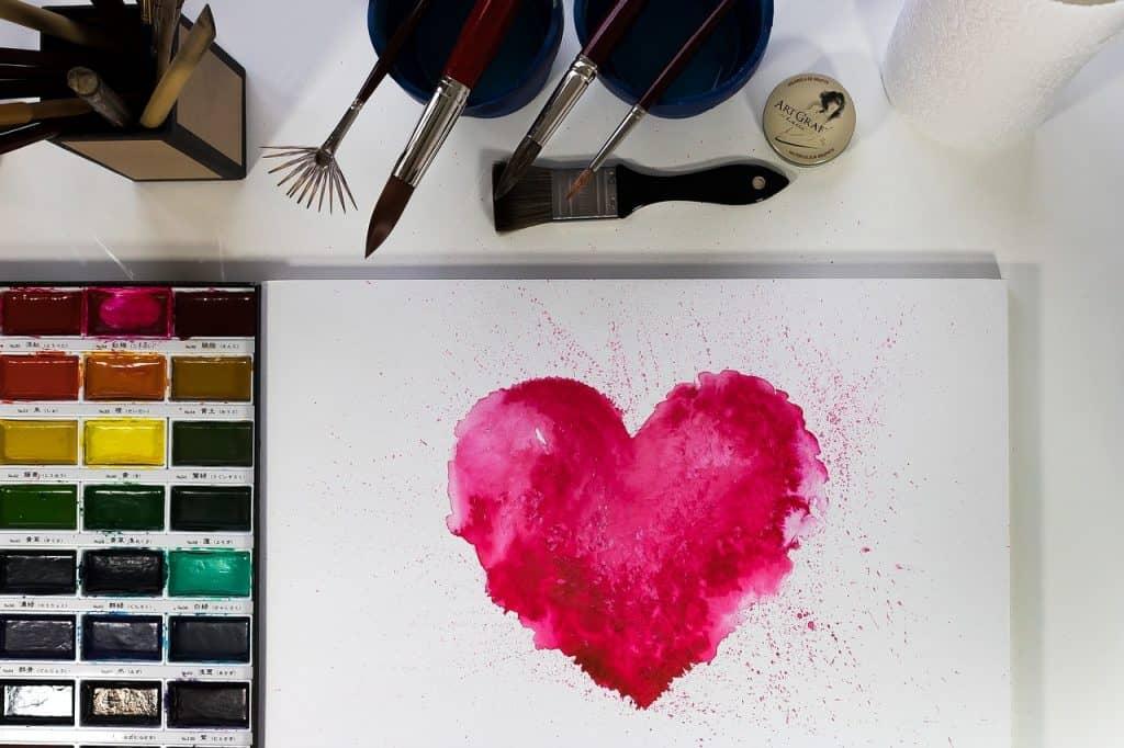 Na foto um coração rosa pintado em um papel com tinta aquarela ao lado de uma paleta de tintas e pincéis.