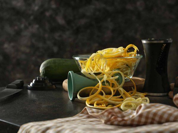 Imagem de cortadores de legumes sobre mesa com legumes.