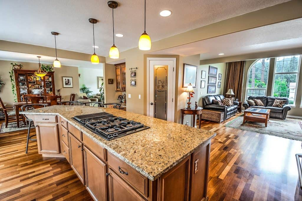 Imagem mostra uma cozinha americana com fogão elétrico em cima de bancada.