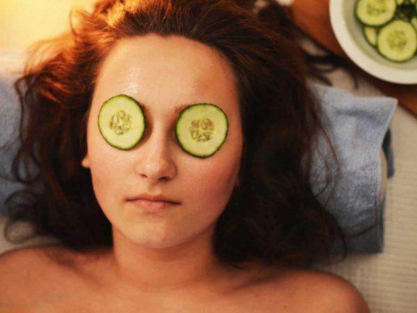 Mulher de cabelo castanho deitada com creme no rosto e pepino nos olhos.