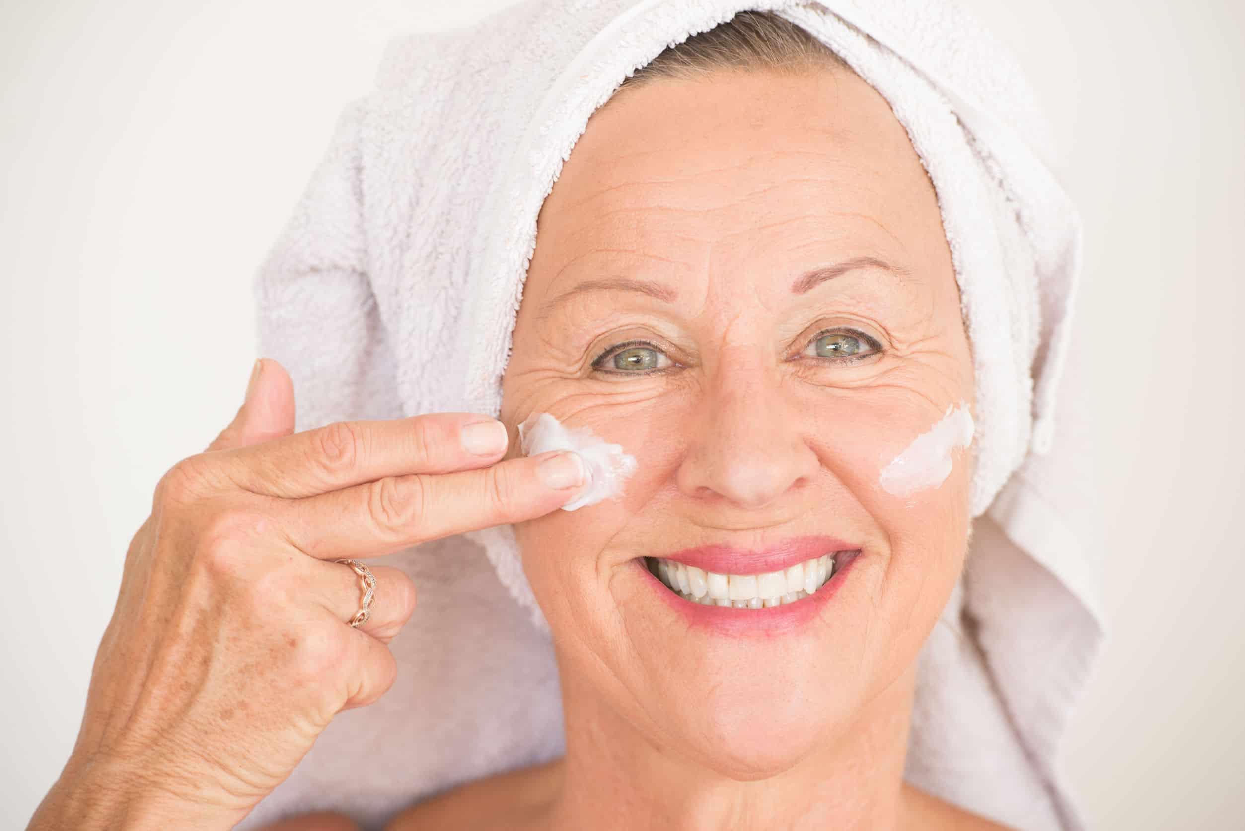 Mulher idosa com toalha de banho enrolada na cabeça aplicando creme para rugas no rosto.