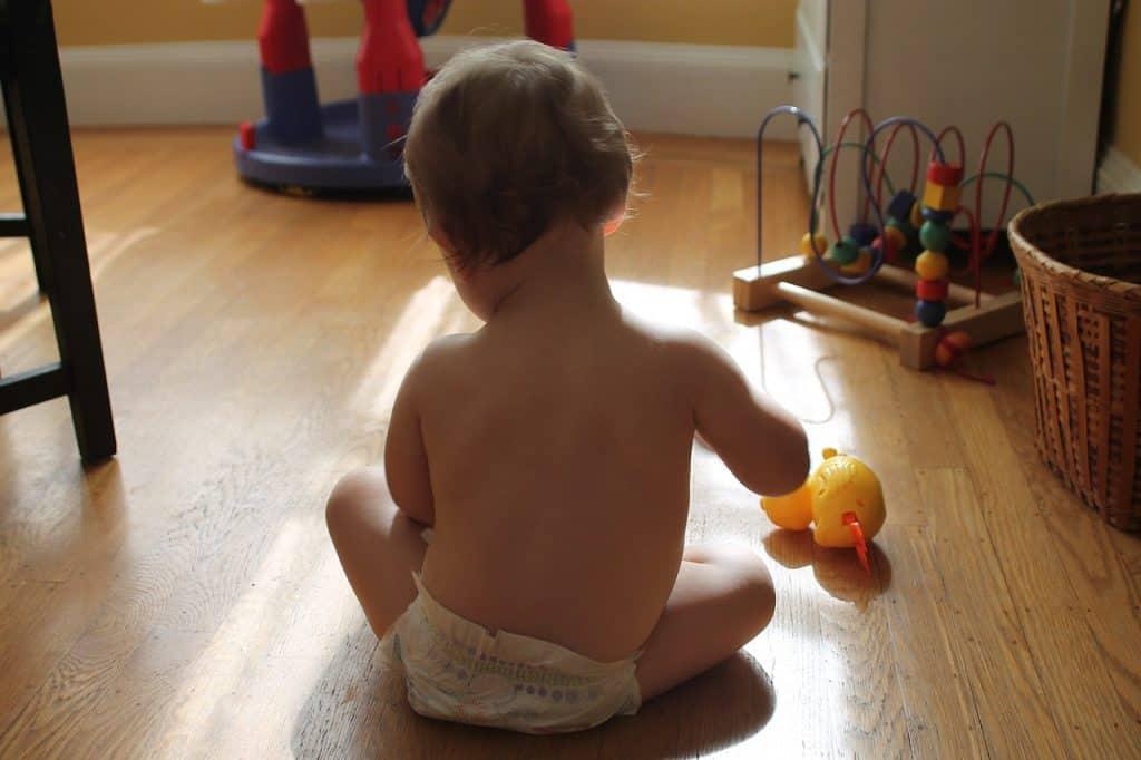 Bebê brinca no chão de casa, sem a segurança que o cercadinho traz.