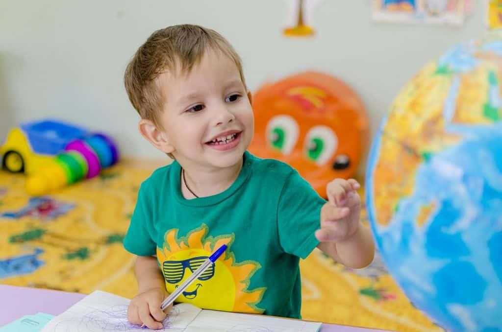 Imagem mostra um menino com um globo terrestre.