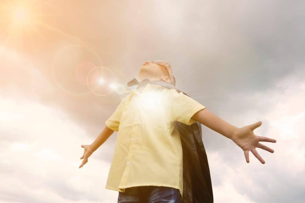 Na foto um menino vestido com uma capa como a de um super-herói.