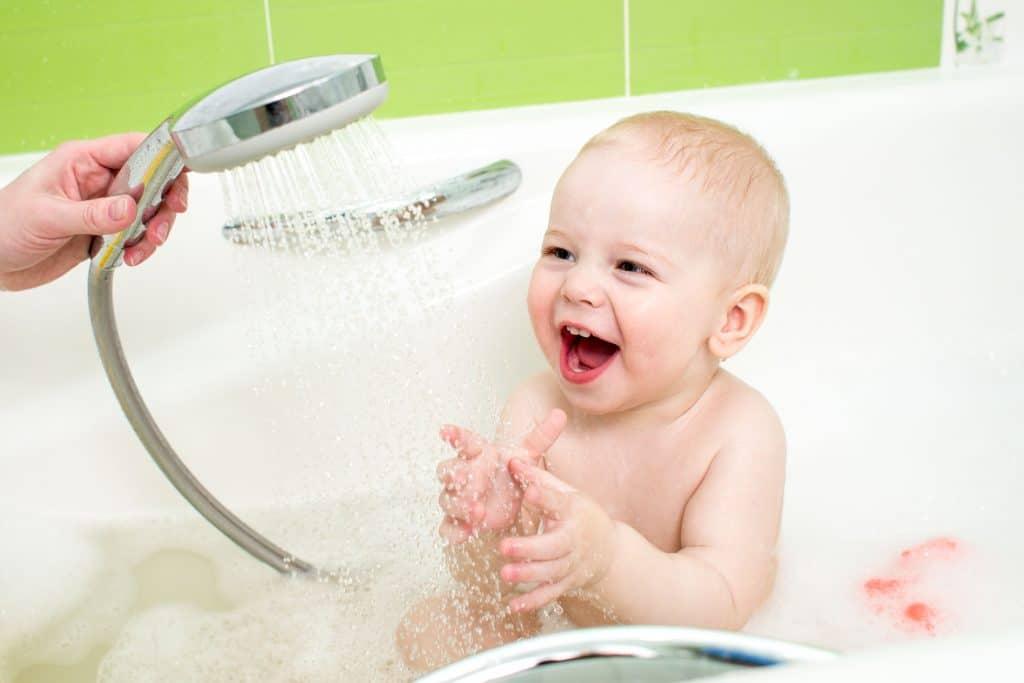 Imagem de criança tomando banho com ducha.