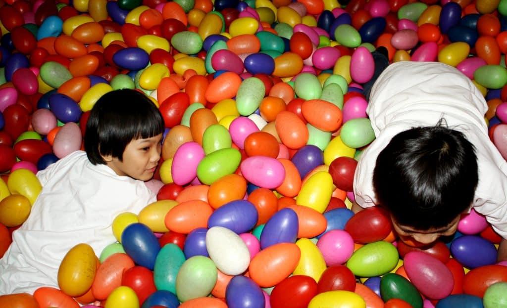 Imagem mostra duas crianças em uma piscina de bolinhas.