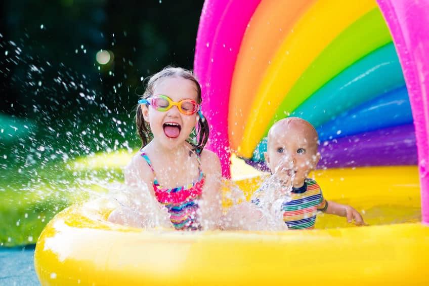 Imagem de crianças brincando de jogar água em piscina infantil.