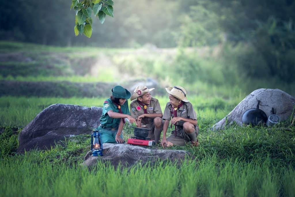 Imagem de três crianças com uniforme de escoteiro sorrindo em volta de um fogareiro.