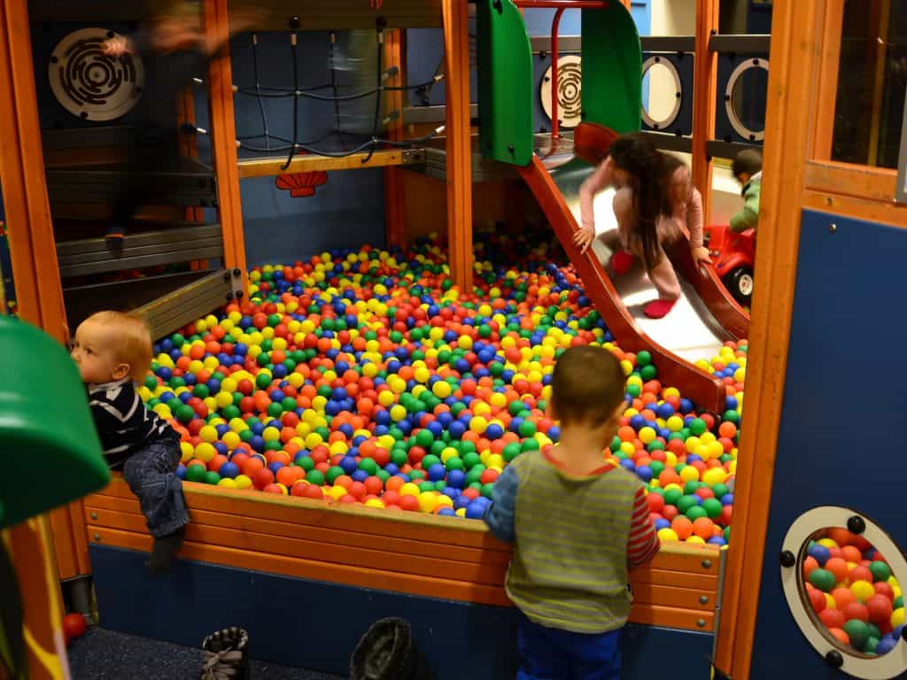 Imagem mostra uma piscina de bolinhas com escorregador e túnel e algumas crianças brincando.