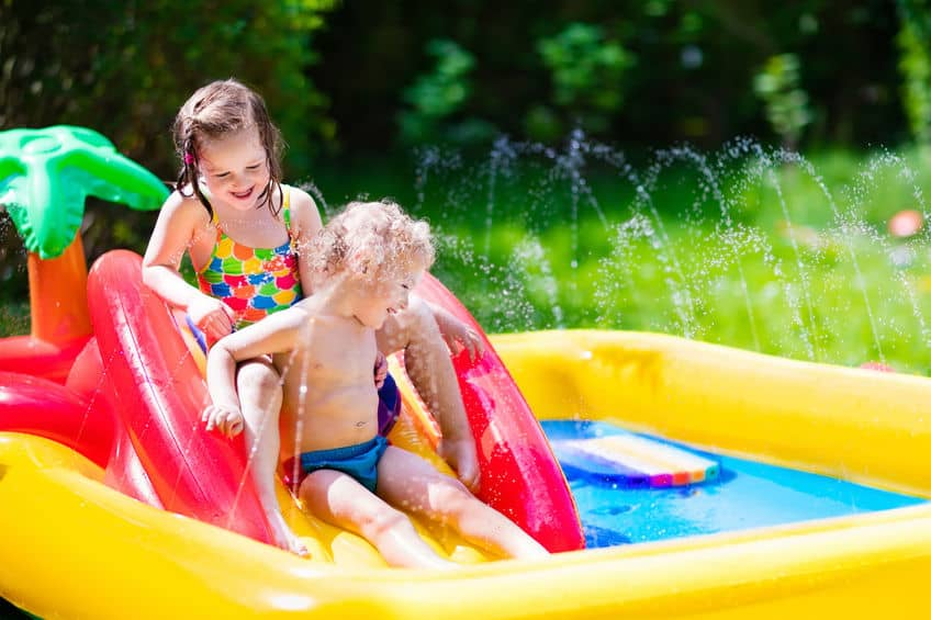 Imagem de duas crianças em escorregador de piscina.