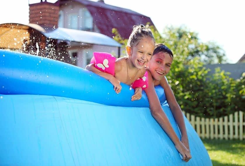 Imagem de duas crianças sorrindo em borda de piscina.