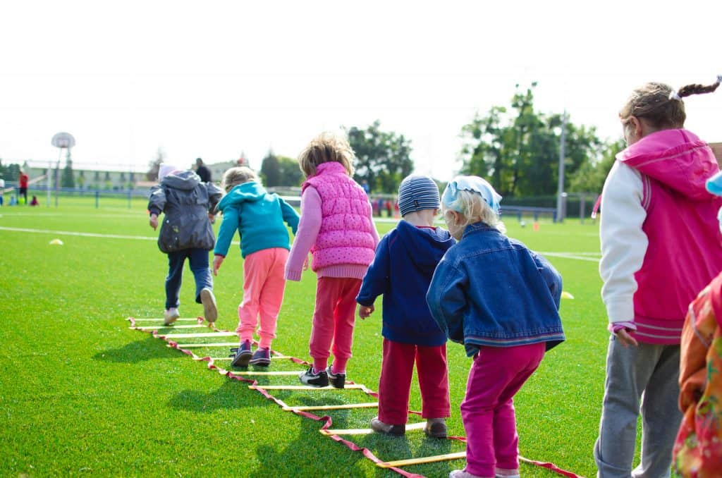 Na foto está um grupo de crianças em fila se exercitando em uma escada de agilidade no meio de um campo de futebol.