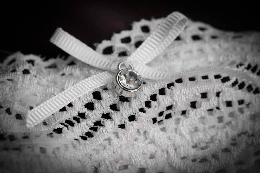 Imagem de calcinha branca sensual com rendas e laço com joia.