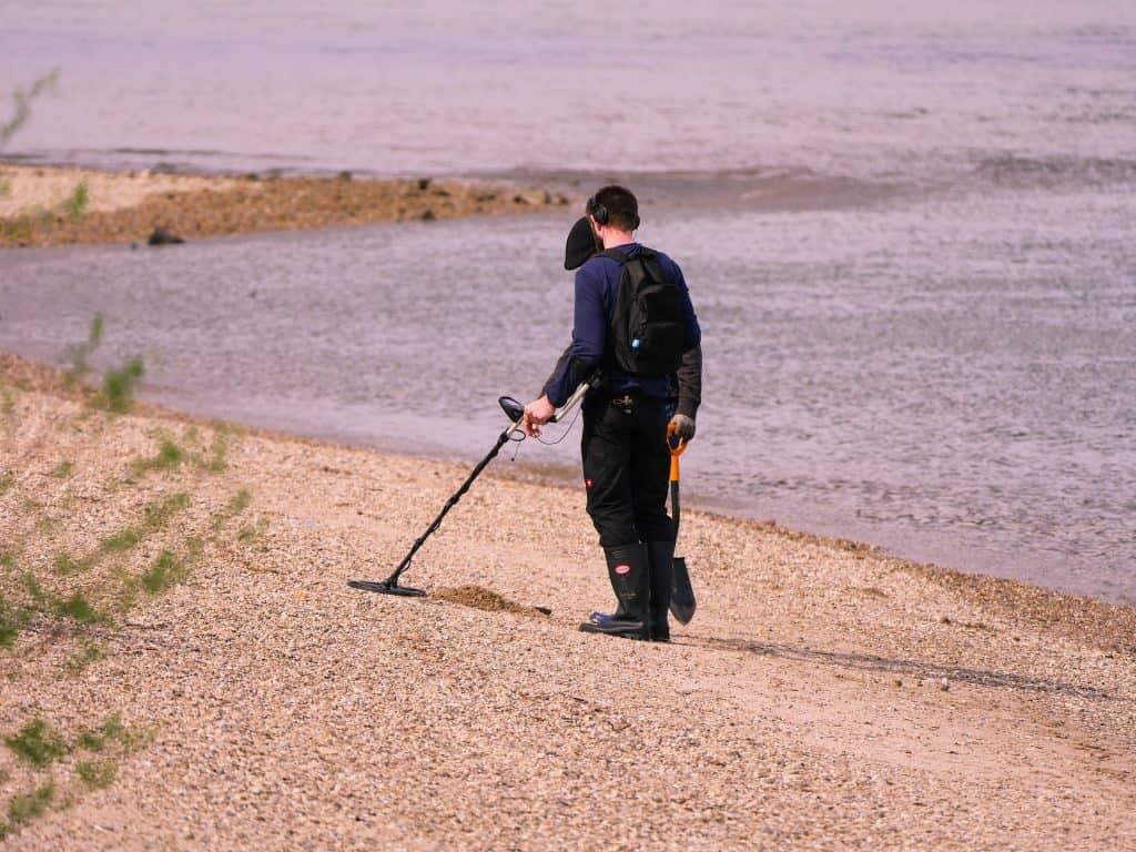 Um homem com um detector de metal na beira do mar.