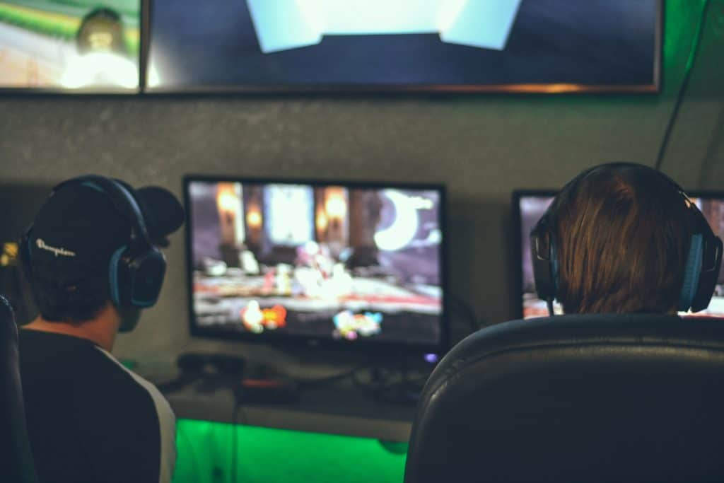 Imagem mostra duas pessoas de costas jogando em frente a dois monitores.
