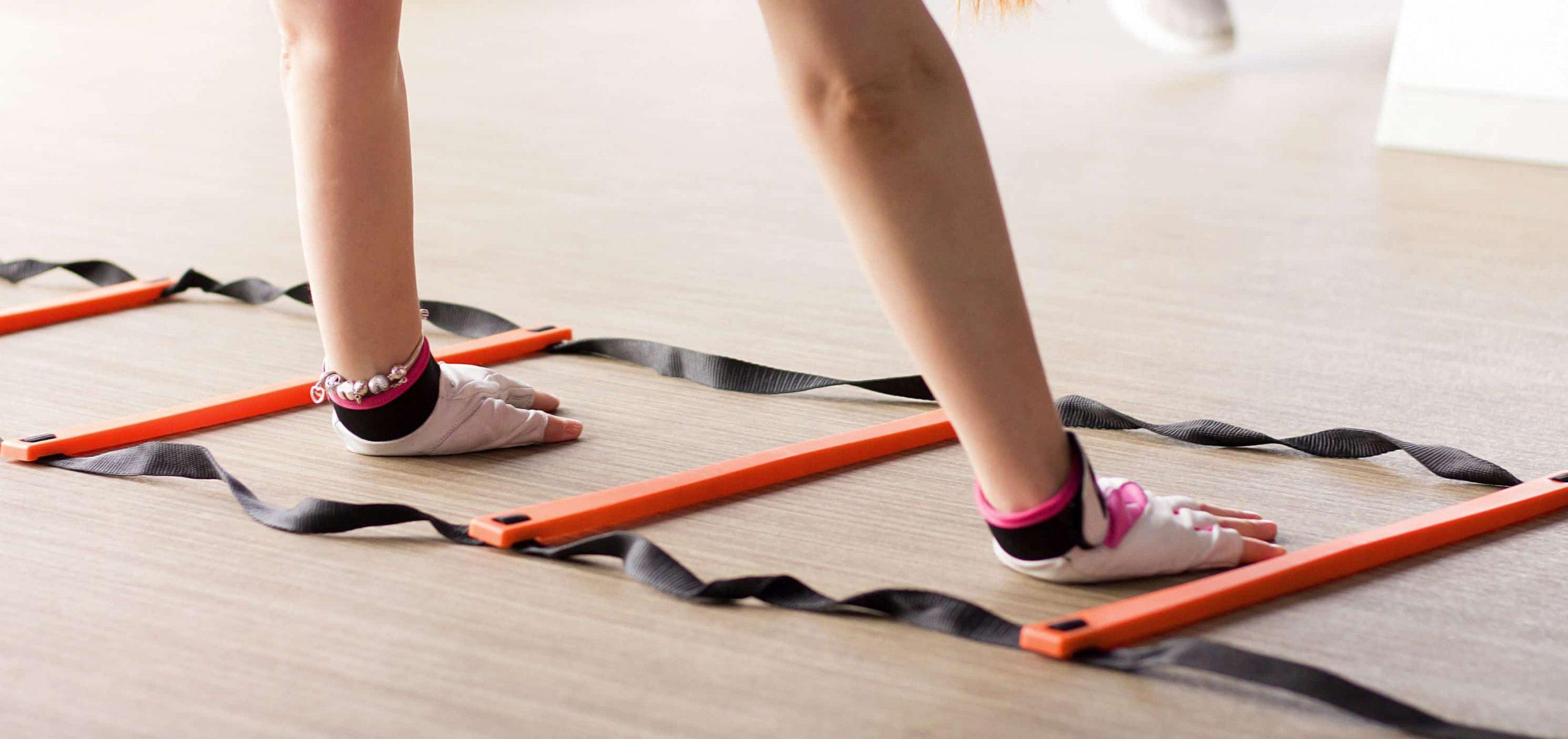 Na imagem está as mãos de uma mulher com luvas de treino dentro de uma escada de agilidade em cima de um chão de madeira.