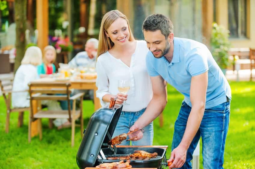 Casal fazendo churrasco no jardim com família de fundo.