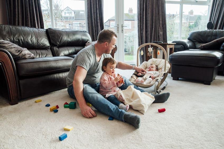 Imagem de pai com filha no colo e bebê em cadeirinha de descanso, no chão da sala.