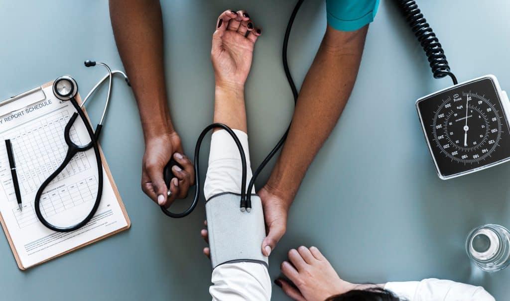 Imagem de uma pessoa medindo a pressão arterial.