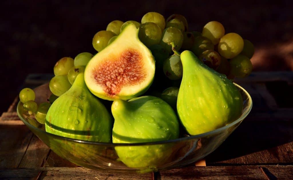Foto de uma fruteira de vidro, contendo três figos inteiros, um figo partido ao meio e cachos de uva.