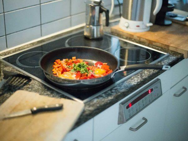 Imagem mostra frigideira em cima de um fogão elétrico.